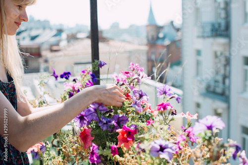 Young woman on a balcony gardening Wallpaper Mural