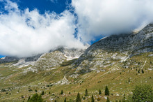 Mountain Peaks Above The Montasio Plateau, Partly Covered By Fluffy Clouds In Summer.