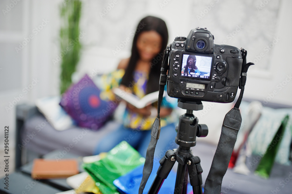 Fototapety, obrazy: Cute african american woman making a video for her blog using a tripod mounted digital camera. Young female blogger or vlogger on camera.