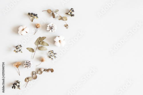 Winter composition. Dried leaves, cotton flowers, berries, pine cones on gray background. Autumn, fall, winter concept. Flat lay, top view, copy space - 295044754