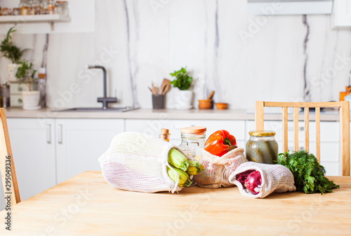 Obraz Kitchen interiour and table with groceries in textile bags - fototapety do salonu