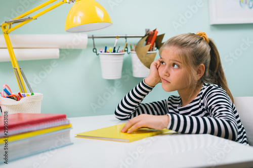 Fotomural tiresome schoolgirl sitting desk at her room and studying
