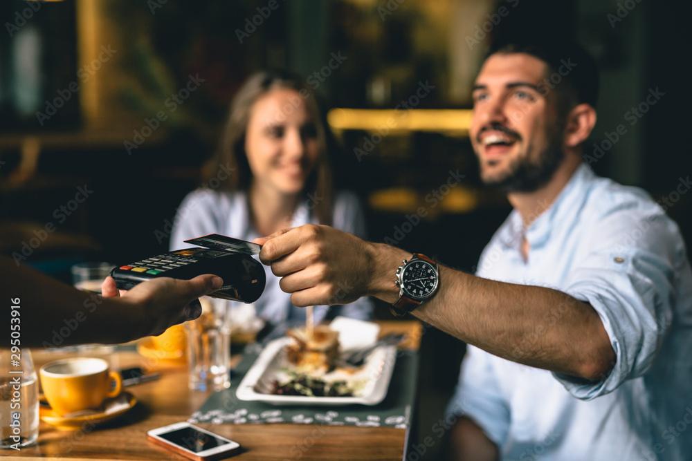 Fototapeta man paying bill at fancy restaurant