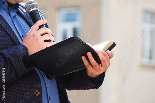 Fotografie, Obraz A preacher with a microphone in his hand holds a Bible and reads a passage from