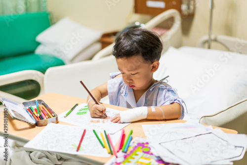 The patient boy is painting the paper with a color pencil in the hospital Fototapete
