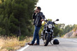 Man biker talking on the phone to the insurance of his motorcycle after having suffered a breakdown on the road.