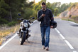 Man biker walking on the road while using her mobile phone after having suffered a breakdown on the road.