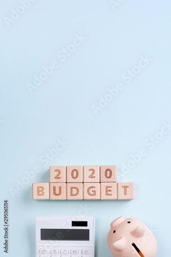2020 goal, finance plan abstract design concept, wood blocks on blue table background with piggy bank and calculator, top view, flat lay, copy space. - 295065114