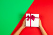 canvas print picture - Kid hands holding present gift box with ribbon on red and green background. Congratulations with Christmas, mother's day, Valentine's day, happy birthday