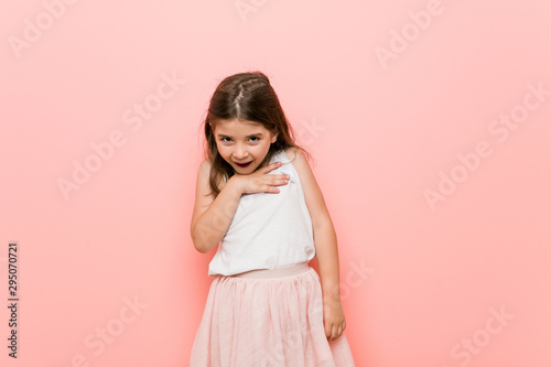 Obraz na plátně  Little girl wearing a princess look laughs out loudly keeping hand on chest
