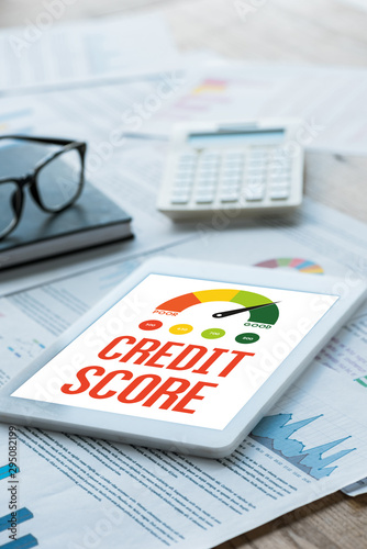 selective focus of digital tablet with credit score lettering near notebook and glasses on documents - 295082199