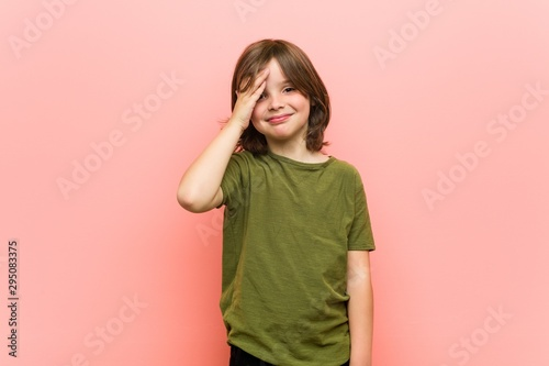 Fotomural  Little boy blink at the camera through fingers, embarrassed covering face