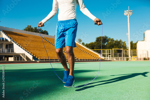 Fototapeta Close up African American sportsman jumping on skipping rope during workout at stadium obraz