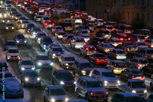 Fototapety, obrazy: Car traffic jams due to snowfall in the evening.
