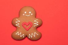 Christmas Gingerbread Man Biscuit With Red Heart Icing On Red Background