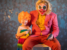 Portrait Of Male Clown In Pink Dressed For Halloween. Actor Made Makeup Crazy Evil Clown With Bloody Smile. White Face Makeup. Model In Halloween Costume With Baby Charming Girl In Colour Clothes