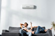 canvas print picture - attractive girlfriend switching on air conditioner and lying on legs of handsome boyfriend