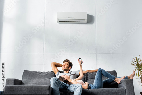 attractive girlfriend switching on air conditioner and lying on legs of handsome Wallpaper Mural