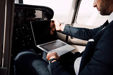 Partial View Of Businessman In Formal Wear Using Laptop With Blank Screen In Plane
