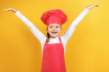 Happy Beautiful Little Girl Chef On A Yellow Background. The Child Raised His Hands Up