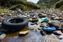 Car Tire And Plastic Bottles In Muddy Puddle On Beach. Beach Waste Pollution From Ocean.