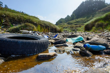Earth Plastics Pollution Global Enviroment Emergency. Old Car Tire In Dirty Water With Plastic Bottles And Trash.