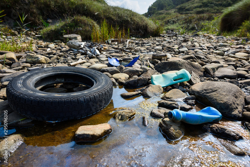Foto Car tire and plastic bottles in muddy puddle on beach