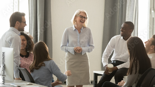 Mature female team leader having fun with coworkers in office - 295096914