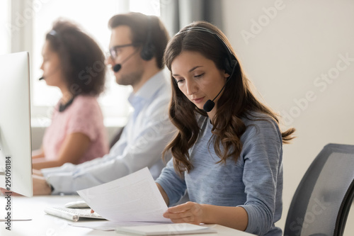 Customer support phone operator sitting at workplace holds read document - 295098184