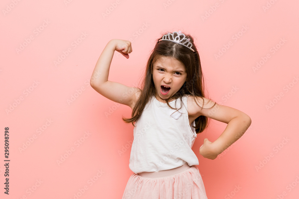Fototapeta Little girl wearing a princess look raising fist after a victory, winner concept.