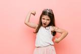 Little girl wearing a princess look raising fist after a victory, winner concept.
