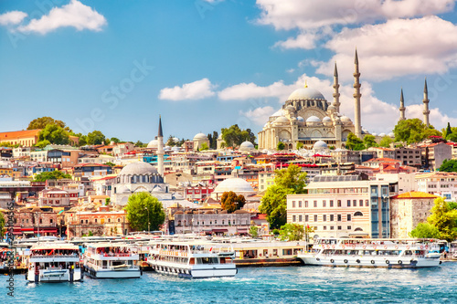 Fotomural  Touristic sightseeing ships in Golden Horn bay of Istanbul and view on Suleymaniye mosque with Sultanahmet district against blue sky and clouds