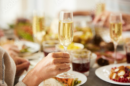 Bar Close-up of female hand holding glass with champagne while have dinner at the table