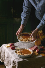 Traditional Homemade Autumn Pumpkin Pies In Man's Hands For Thanksgiving Or Halloween Dinner Served In Ceramic Dish With Yellow Autumn Leaves, Pumpkins On Linen Table Cloth. Dark Rustic Style