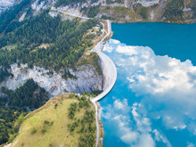 Water Dam And Reservoir Lake In Swiss Alps To Produce Hydropower, Hydroelectricity Generation, Renewable Energy, Aerial Drone Photography