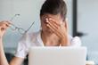 Leinwandbild Motiv Stressed tired young business woman holding glasses feeling headache