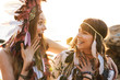 canvas print picture - Image of joyous girls wearing indian chief feather headdress by seaside
