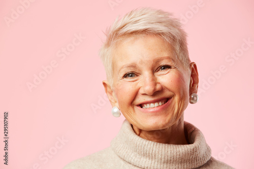 Portrait of beautiful happy mature woman smiling at camera over pink background Canvas Print