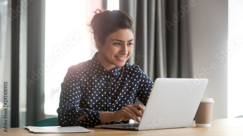 Obraz na plátně Happy young indian businesswoman using computer sit at office desk
