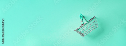 Top view of supermarket shopping basket on trendy green background Fototapete