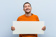 canvas print picture - Young caucasian man holding a placard happy, smiling and cheerful.