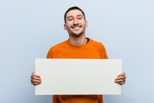 Young Caucasian Man Holding A Placard Happy, Smiling And Cheerful.