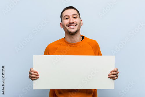 Fototapeta Young caucasian man holding a placard happy, smiling and cheerful. obraz