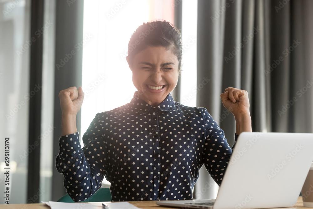 Fototapeta Happy overjoyed indian business woman winner celebrate computer win