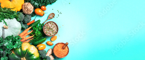 Fototapeta Organic vegetables, lentils, beans, raw ingredients for cooking on trendy green background. Healthy, clean eating concept. Vegan or gluten free diet. Copy space. Top view. Food frame obraz