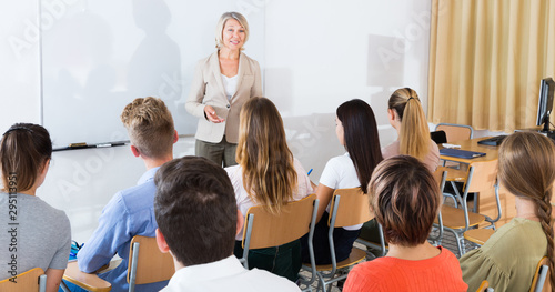 Pinturas sobre lienzo  Mature female giving presentation for students