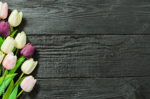 Beautiful Tulip flowers on a dark, black wooden textured background. Spring bouquet. Flat lay, top view, copy space. - 295114967