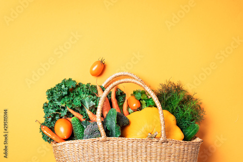 Straw basket with organic vegetables over trendy yellow background Fototapet