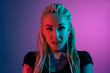 canvas print picture - Caucasian young woman's portrait on gradient background in neon light. Beautiful female model with unusual look. Concept of human emotions, facial expression, sales, ad. Astonished, excited.