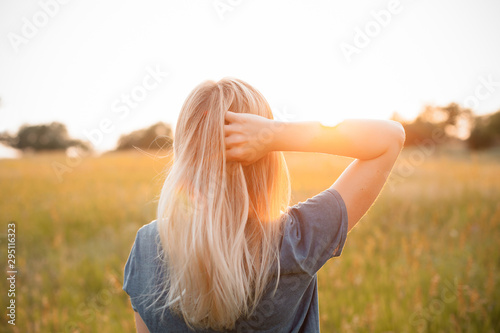 Fotografia Young woman with blonde hair standing on the field and looking on the sunset